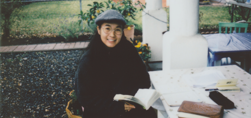 Author sitting in her front yard posing with a book